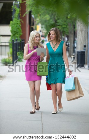 Pretty young women with shopping bags using digital tablet on sidewalk - stock photo