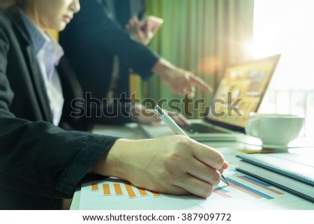 Preview Save to a lightbox Find Similar Images Share close up of business woman hand working on laptop computer with business graph information diagram on office desk as concept in morning light - stock photo