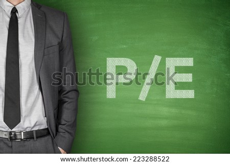 price per earning ratio on green blackboard with businessman - stock photo