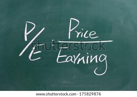 price per earning ratio written on blackboard  - stock photo