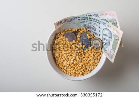 Price rise in basic food and pulses in India. 100 Rupees currency notes and coins in the bowl of Tur Dal. - stock photo
