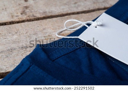 price tag t-shirt on wood background - stock photo