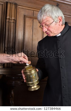 Priest collecting money in church for fund-raising - stock photo