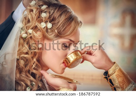 priest gives wine to a crowned bride during orthodox wedding ceremony  - stock photo