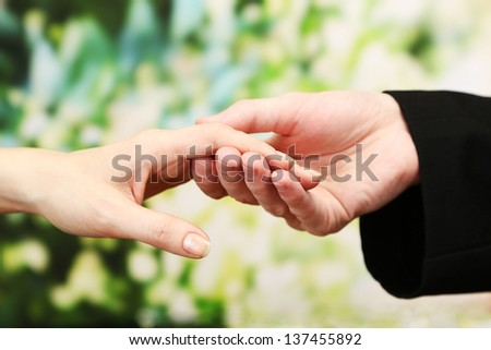 Priest holding woman hand, on green background - stock photo