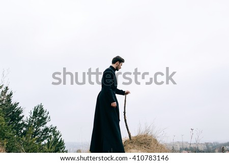 Priest in the mountains above the sinful city - stock photo
