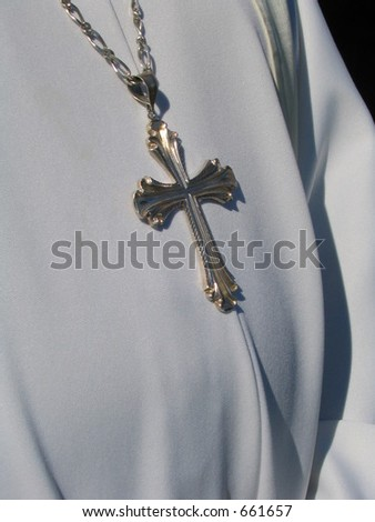 priest in white robes wearing  silver cross - stock photo