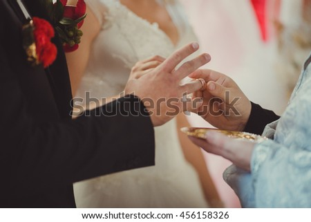 Priest is giving a golden wedding ring to the groom