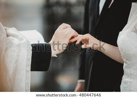 Priest puts a wedding ring on bride's elegant hand