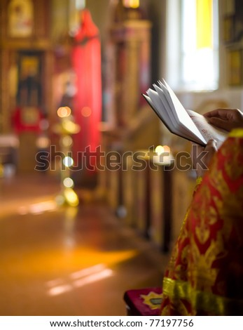 priest reading bible in Russian Orthodox church interior - stock photo