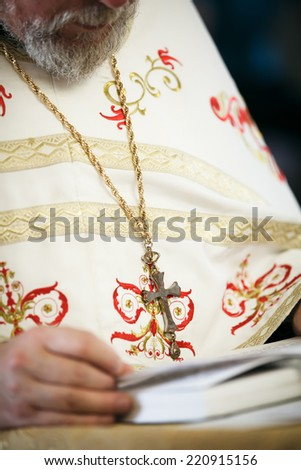 Priest reads a prayer book. Shallow depth of field. Focused on cross - stock photo