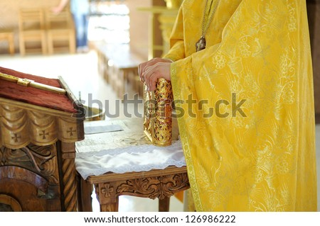 priest's hands holding golden bible - stock photo