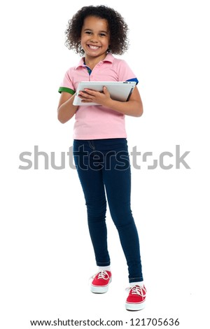 Primary child with a tablet pc smiling cheerfully. Indoor shot over white. - stock photo