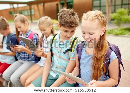 primary education, friendship, childhood, technology and people concept - group of happy elementary school students with backpacks sitting on bench and talking outdoors