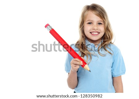 Primary school child posing with a big red pencil in hand,flashing a toothy smile. - stock photo