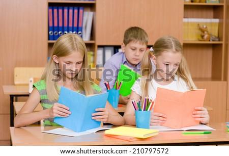 primary school children in the classroom reading books - stock photo