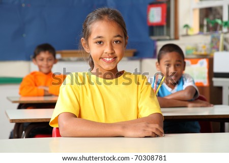 Primary school children sitting to desks in class - stock photo