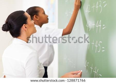 primary school maths teacher teaching student in classroom - stock photo