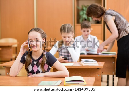 Primary school pupil using cell phone at lesson - stock photo