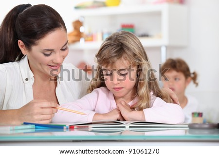 Primary school teacher with young girl - stock photo