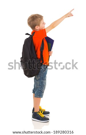 primary schoolboy pointing at empty copyspace isolated on white - stock photo