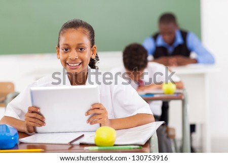 primary schoolgirl using a tablet computer in classroom - stock photo