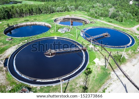 Primary sedimentation stage, sewage flows through large tanks with mechanically driven scrapers - stock photo