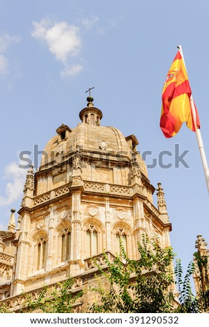 Primate Cathedral of Saint Mary of Toledo, Spain and the Spanish national flag - stock photo