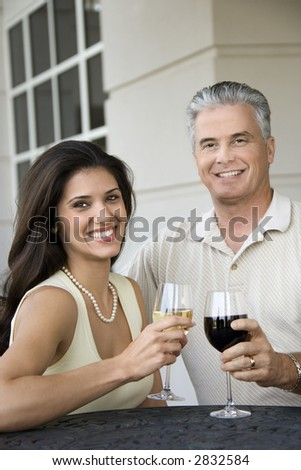 Prime adult Hispanic female and Caucasian prime adult male toasting sitting at table. - stock photo