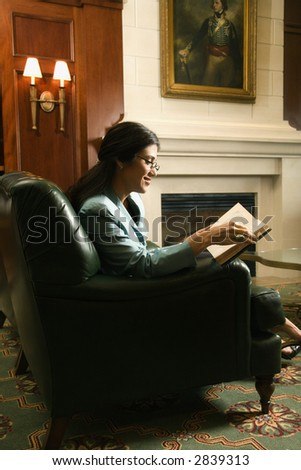 Prime adult Hispanic female sitting and reading.