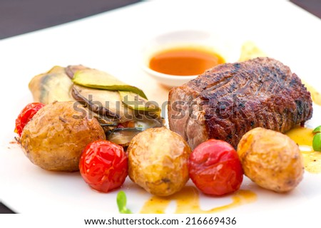 Prime grilled juicy beef steak with roasted vegetables. Outdoors close-up. - stock photo