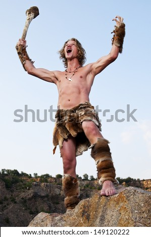 Primitive man holding a club and growling - stock photo