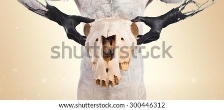 Primitive man holding horse skull over ocher background - stock photo