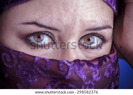 Princess, Beautiful arabic woman with traditional veil on her face, intense look - stock photo