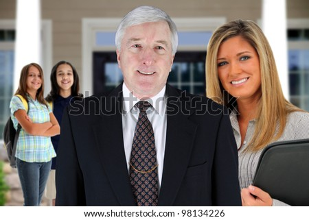 Principal with teacher and students at school - stock photo
