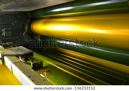 print machine printing press rollers, yellow color drum, dramatic light - stock photo