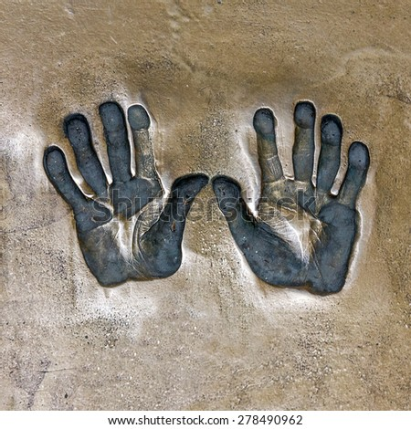 Print of hands. Both hands print on cement mortar wall with shadow relief - stock photo