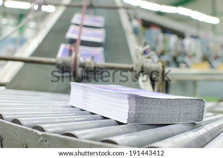 Print shop (press printing) - Finishing line. Post press finishing line machine: cutting, trimming, paperback and binding - stock photo