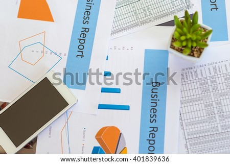 Printed Business Annual Report in Charts ,thai banknote and smartphone .business concept. - stock photo