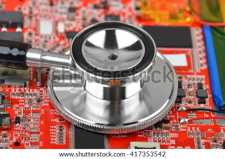 Printed computer motherboard and stethoscope, diagnostic service concept - stock photo
