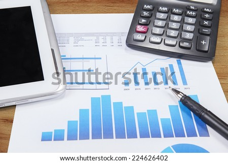 Printed data sheet with pen, calculator, and digital tablet on the table - stock photo