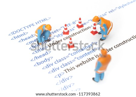 Printed HTML code of website (internet page) under construction. Construction worker figurines working on code. - stock photo