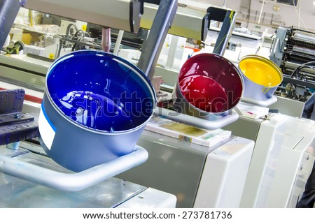 printing machine cylinders and printing ink pot with cyan red yellow color - stock photo