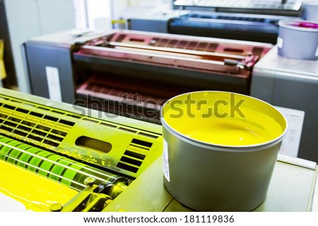 printing machine cylinders and printing ink pot with yellow color - stock photo