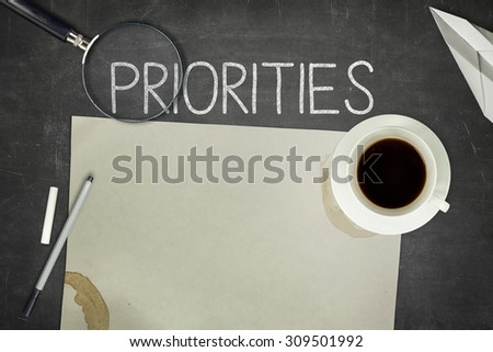 Priorities concept on black blackboard with empty paper sheet - stock photo
