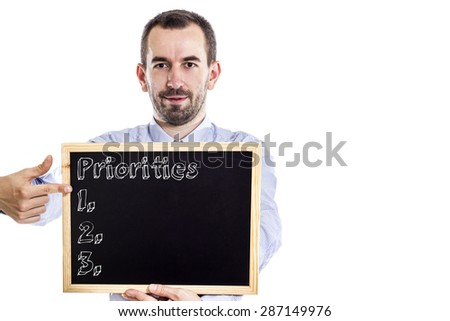 Priorities - Young businessman with blackboard - isolated on white
