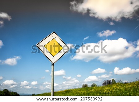 priority road sign with blue sky and clouds