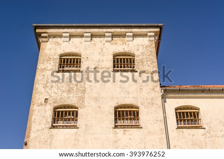 Prison building with bars on windows in spanish style - stock photo
