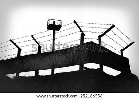 Prison fence with barbed wire, black and white grunge version - stock photo