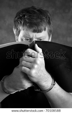 Prisoner finds comfort by studying the Holy Bible while in handcuffs. - stock photo